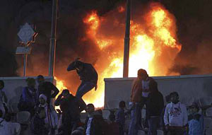 A soccer fan flees from a fire at Cairo stadium