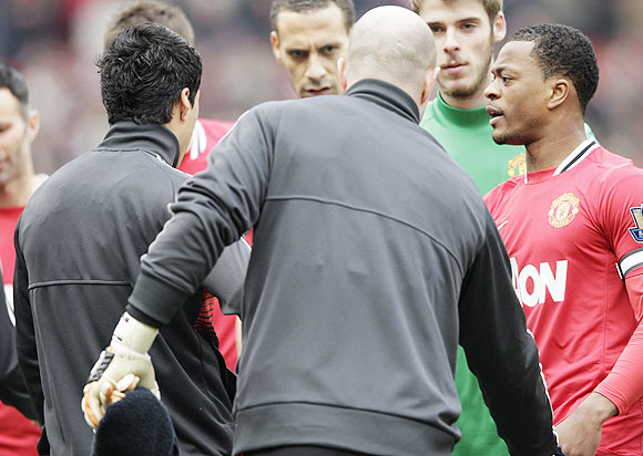 Manchester United's Patrice Evra (right) reacts after Liverpool's Luis Suarez (left) ignored his handshake