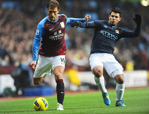 Aston Villa's Stiliyan Petrov is tackled by Man City's Sergio Aguero