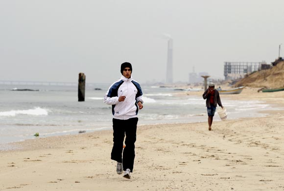 Gaza runner Bahaa al-Farra trains on a beach in Gaza City