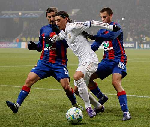 Real Madrid's Mesut Ozil fends off the challenges from CSKA Moscow players during the UEFA Champions League round of 16, first leg match at the Luzhniki Stadium