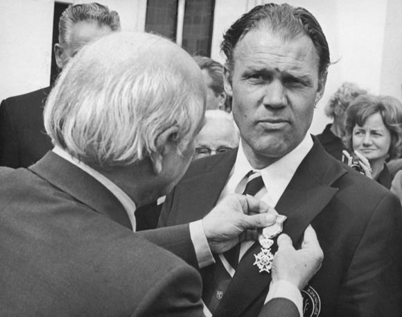 Dutch football coach Rinus Michels (1928 - 2005), inventor of 'total football', receives the Royal distinction from Dutch prime minister Joop Den Uyl at the Hague, 1974