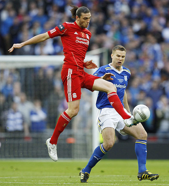 Liverpool's Andy Carroll (left) challenges Cardiff City's Ben Turner