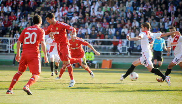 Cristiano Ronaldo (2nd L) of Real Madrid scores his team's opening goal during the La Liga match between Rayo Vallecano and Real Madrid at Estadio Teresa Rivero