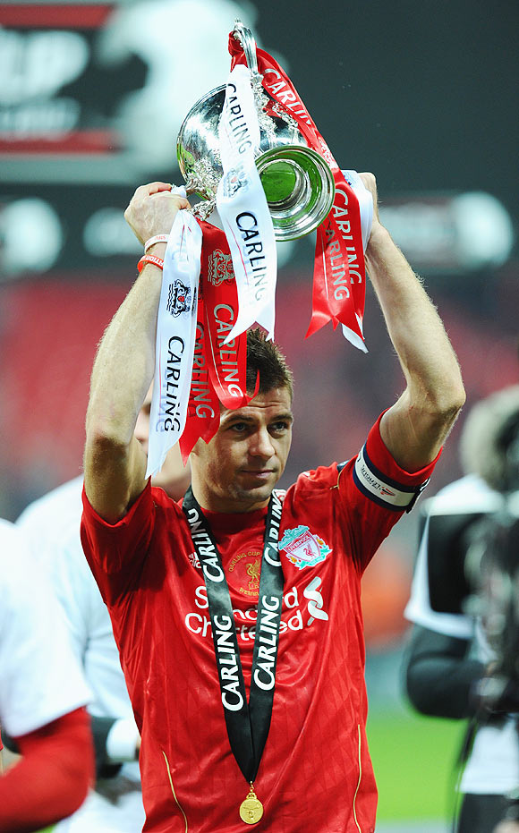 Steven Gerrard of Liverpool celebrates with the trophy after victory in the Carling Cup final on Sunday