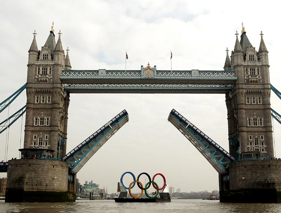 The giant Olympic rings are towed on The River Thames past The Tower of London