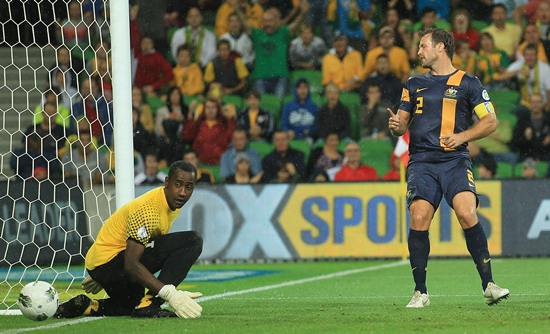 Lucas Neill heads past the Saudi goalkeeper