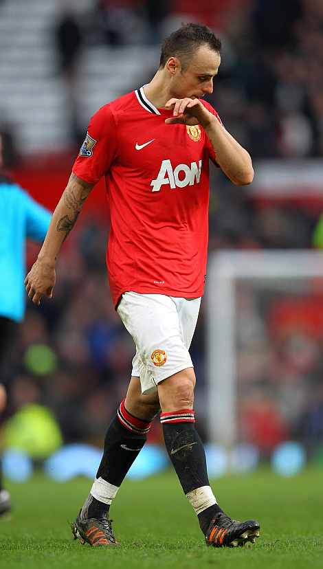 Manchester United's Dimitar Berbatov walks off dejected after losing 3-2
