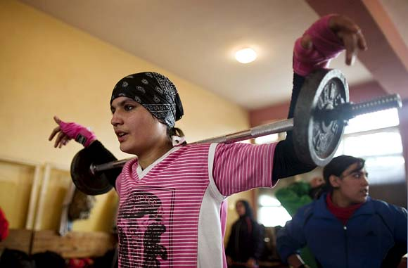 Sadaf Rahimi lifts weights during a practice session in a boxing club in Kabul