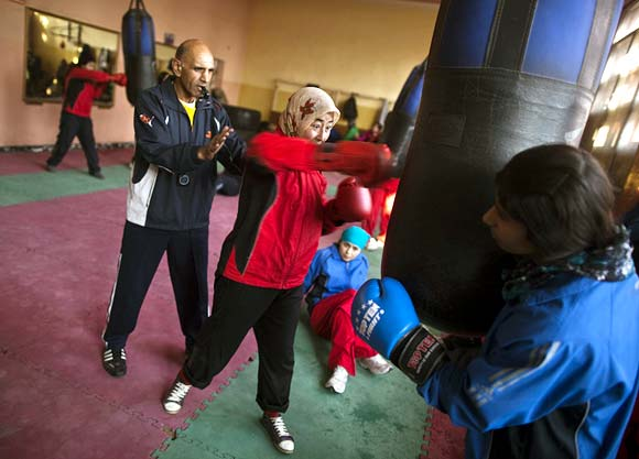 An Afghan woman punches a bag during a practice session inside a boxing club in Kabul