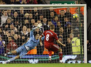Liverpool's Steven Gerrard (right) shoots to score a penalty past Oldham Athletic's Alex Cisak on Friday