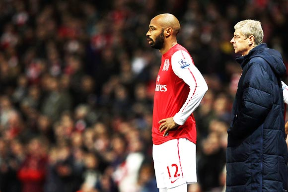 Thierry Henry prepares to come on as a substitute as manager Arsene Wenger looks on