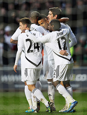 Scott Sinclair of Swansea City is congratulated by teammates after scoring his penalty against Arsenal on Sunday