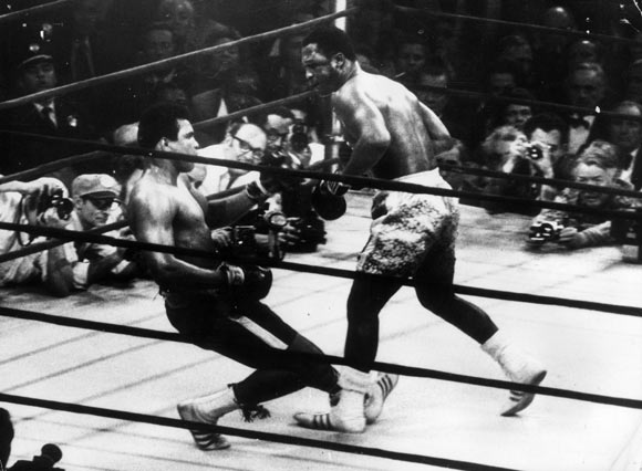 In a fight at Madison Square Gardens in 1971, Ali goes down in the 15th round to a left hook from heavyweight champ Joe Frazier who kept the title.