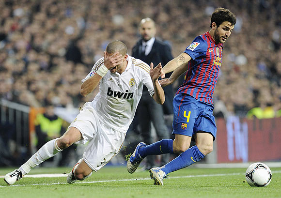 Real Madrid's Pepe (left) falls next to Barcelona's Cesc Fabregas during their King's Cup quarter-final first leg match on Wednesday
