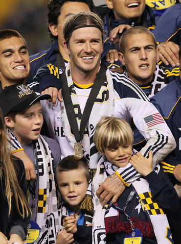 David Beckham #23 of the Los Angeles Galaxy celebrates with his sons Brooklyn, Cruz and Romeo after defeating the Houston Dynamo 1-0 in Carson, California