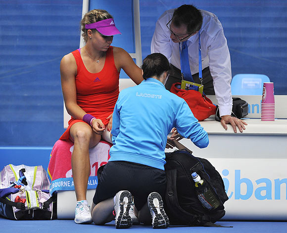Russia's Maria Kirilenko talks with a match and medical official during her match against Petra Kvitova