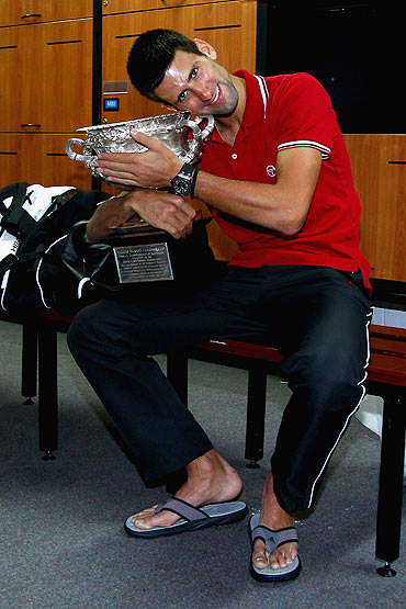 Novak Djokovic of Serbia poses with the Norman Brookes Challenge Cup in the players locker room