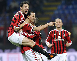 AC Milan's Zlatan Ibrahimovic (centre) celebrates with teammate Mark Van Bommel (left) after scoring against Cagliari during their Serie A match on Sunday
