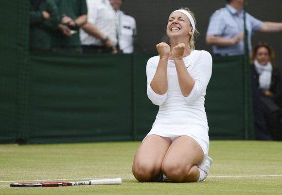 Sabine Lisicki of Germany celebrates after defeating Maria Sharapova of Russia in their women's singles tennis match at the Wimbledon tennis championships in London