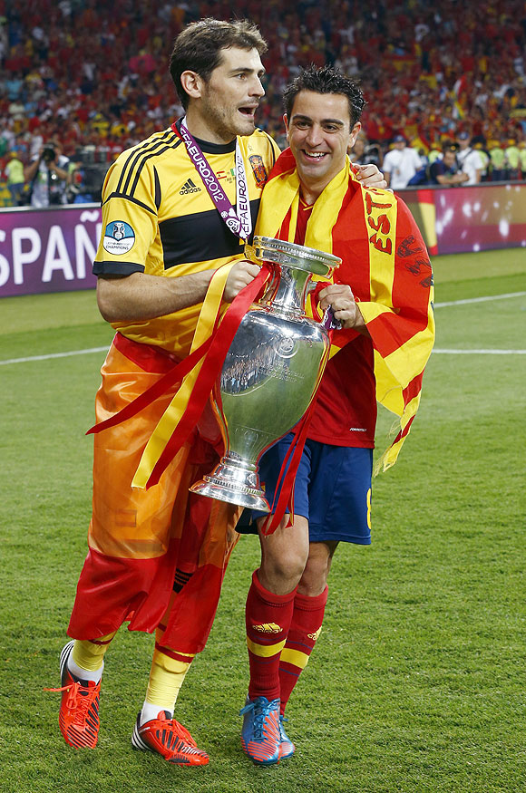 Spain's goalkeeper and captain Iker Casillas and Xavi Hernandez (right) celebrate with the trophy after defeating Italy