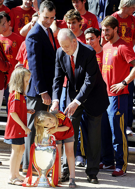Spain's King Juan Carlos and Crown Prince Felipe (second left) looks at Infanta Sofia (bottom right) as she puts her arm into the Euro 2012 trophy next to Infanta Leonor (left) during a visit of the national soccer team members to Madrid's Zarzuela Palace