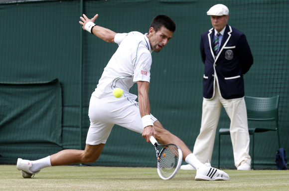 Novak Djokovic of Serbia hits a return to Florian Mayer of Germany during their men's quarter-final tennis match at the Wimbledon tennis championships in London