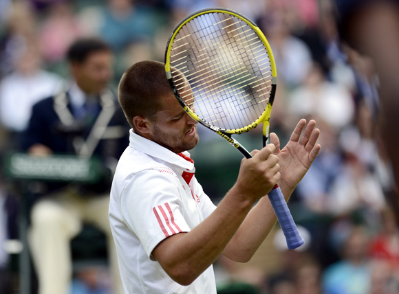 Mikhail Youzhny of Russia reacts during his men's quarter-final tennis match against Roger Federer of Switzerland at the Wimbledon tennis championships in London