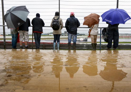 Fans watch in wet and muddy conditions during practice for the British Grand Prix
