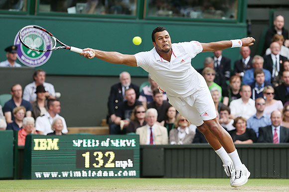 Jo-Wilfried Tsonga of France hits a forehand return against Andy Murray