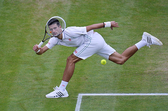 Novak Djokovic hits a return against Roger Federer