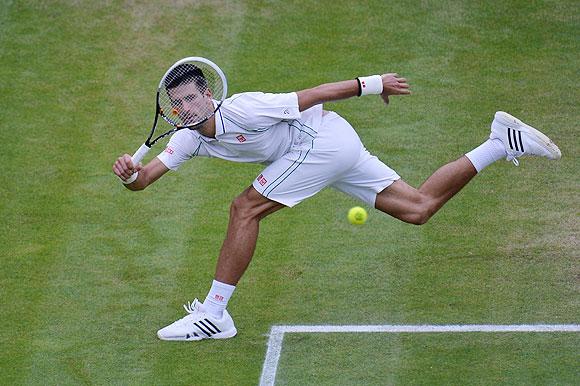 Novak Djokovic hits a return against Roger Federer