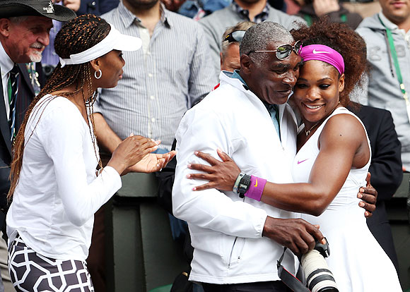 Serena Williams celebrates with her father Richard Williams and sister Venus Williams after her Wimbledon final win over Agnieszka Radwanska
