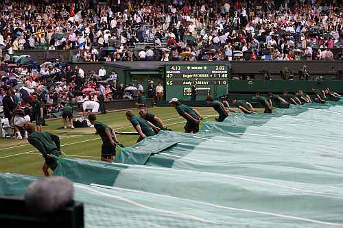 Roger Federer and Andy Murray walk off court as rain delays play and the court is covered during their Men's singles final