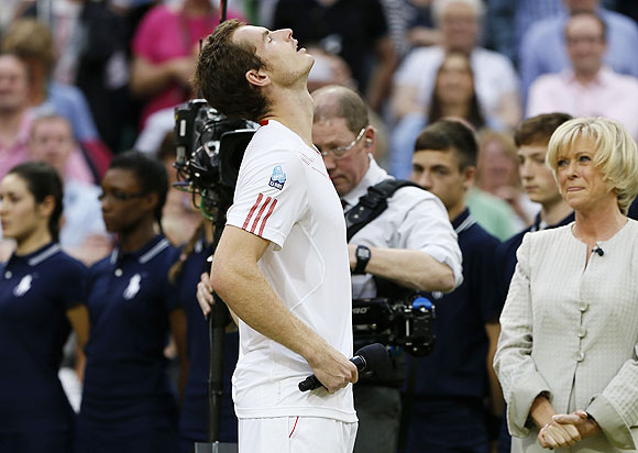 Andy Murray fights to hold back tears during a television interview with Sue Barker (right) after his loss against Roger Federer on Sunday