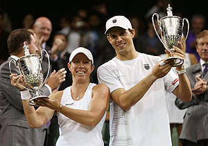 Mike Bryan and Lisa Raymond hold up the winners trophy after beating Elena Vesnina and Leander Paes to win the Mixed Doubles final on Sunday