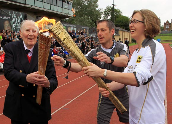 Roger Bannister (left) passes the Olympic flame to Torchbearer  Nicola Byrom on the track at Iffley Road Stadium