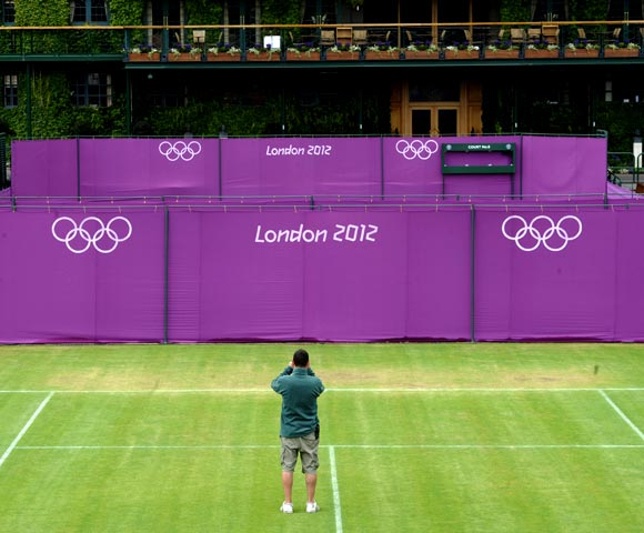 A workman takes a photograph on Court 10 as Olympic hoarding is erected at the All England Lawn Tennis Club (AELTC) as preparations are made for the London 2012 Olympic Games