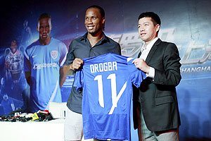 Zhou Jun (right), director of Shanghai Shenhua Football Club, and Didier Drogba hold up a Shanghai Shenhua FC jersey during an unveiling
