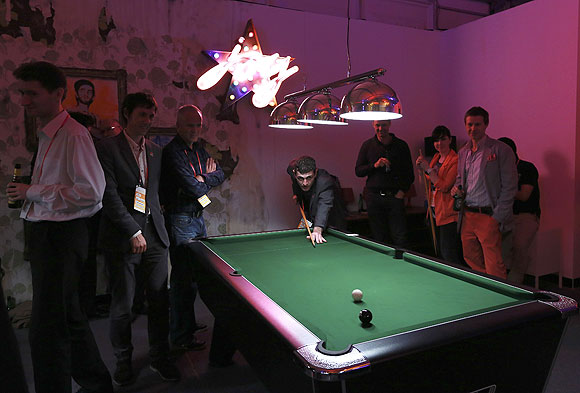 Visitors play pool in the Globe bar in the Olympic Village