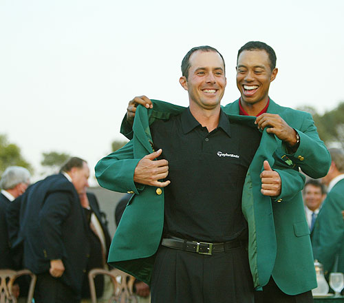Canadian golfer Mike Weir receives his green jacket from former champion Tiger Woods