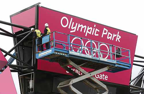 Worker adjusts his position on cherry picker in front of one of the signs at the entrance to the Olympic Park