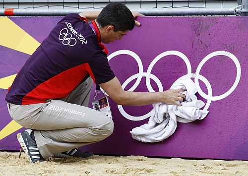 Simon Drew wipes down hoarding surrounding a practice beach volley ball court