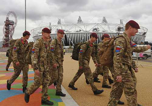 Soldiers pass the Olympic Stadium in the London 2012 Olympic Park in Stratford