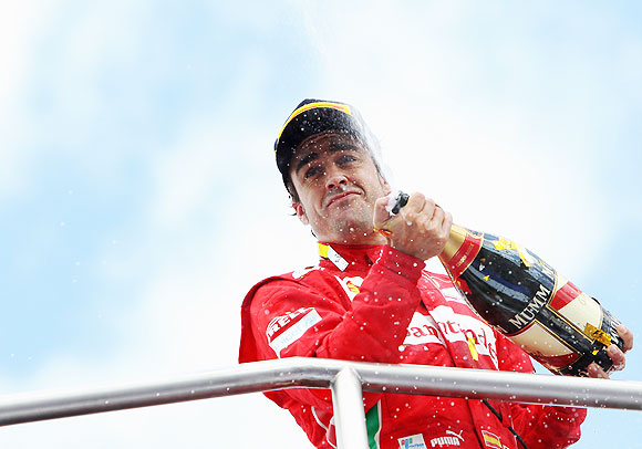 Fernando Alonso of Spain and Ferrari celebrates on the podium