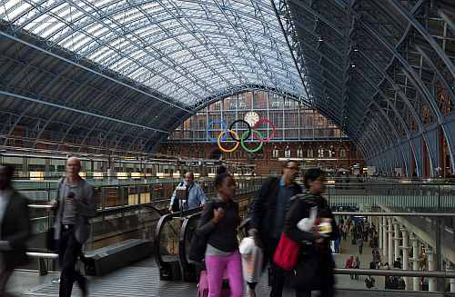 The Olympic Rings are seen as commuters walk in St Pancras Station in London