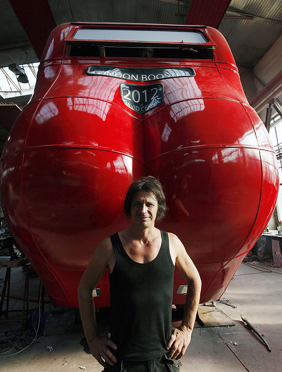 Czech artist David Cerny poses next to a London bus that he has transformed into a robotic sculpture in Prague
