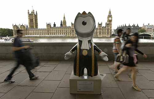 People walk by an Olympic mascot, painted in the likeness of a member of Parliament, across the River Thames