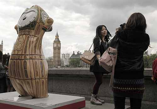 A tourist is photographed in front of Big Ben near an Olympic mascot painted in the likeness of Big Ben