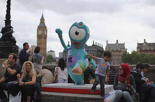 People sit next to a model of a Wenlock, one of the official mascots